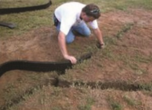 photo of a man installing geo-channel in a yard for yard drainage