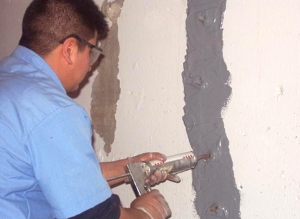 picture of a man applying PolyFoam to fix a basement wall crack