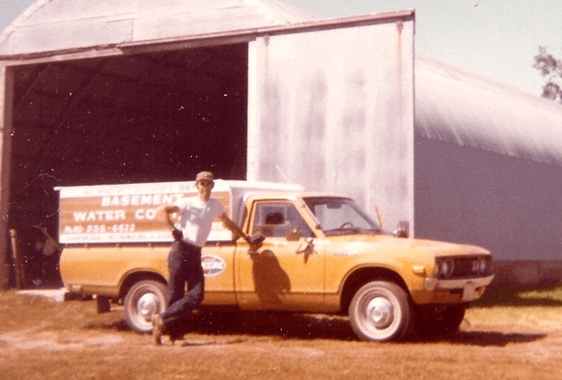 vintage photo of Gary Resch standing by his orange company truck in front of a Quonset building